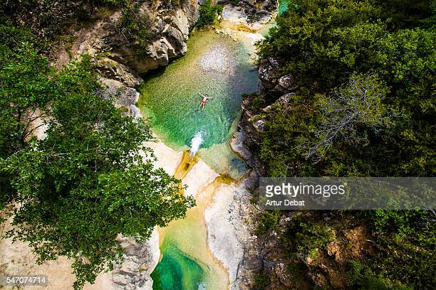 aerial picture of a kid swimming in a paradise green pools created in a creek in the catalan pyrenees during summer. - catalonia stock pictures, royalty-free photos & images