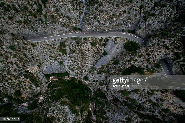 Aerial picture of a mountain road scraped in the rocky mountain with cliff and tunnels in the Catalan Pyrenees.