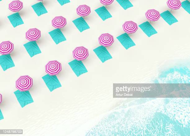 aerial picture of new normal with social distancing in the beach with colorful umbrellas. - beach sunbathing spain stock pictures, royalty-free photos & images