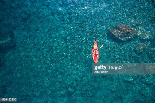 aerial picture of two girls practicing kayak in a paradise place of the costa brava beach with beautiful and transparent blue water on summertime. - aerial view photos stock photos and pictures