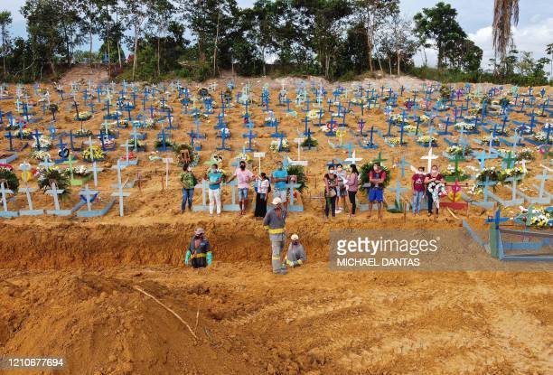TOPSHOT Aerial picture showing a burial taking place at an area where new graves have been dug up at the Nossa Senhora Aparecida cemetery in Manaus...