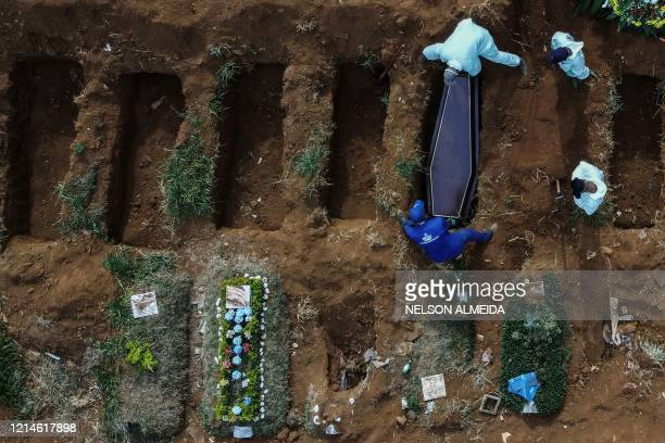 Aerial picture showing gravediggers burying an alleged COVID-19 victim at the Vila Formosa Cemetery, in the outskirts of Sao Paulo, Brazil on May 22,...