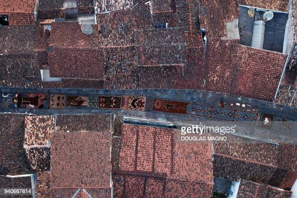 TOPSHOT Aerial picture showing sawdust rugs seen between tiled rooftops decorating a street in the Brazilian historic city of Ouro Preto Minas Gerais...