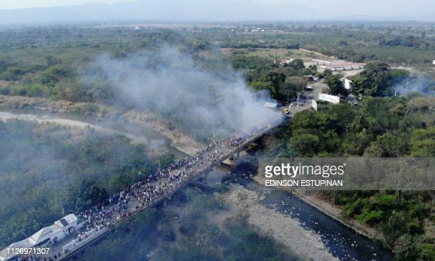 TOPSHOT Aerial picture showing smoke billowing from trucks which were carrying humanitarian aid and which were set ablaze on the Francisco de Paula...