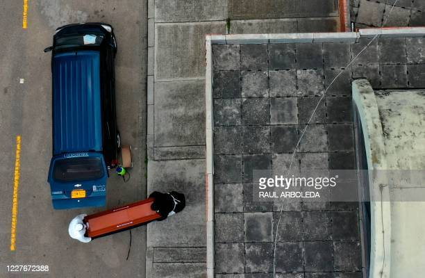 Aerial picture showing workers of a funeral home carrying a coffin before the cremation of a victim of the novel coronavirus COVID19 at the Serafin...