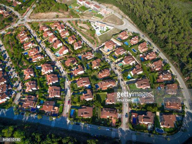 Aerial picture taken directly above of a stunning city pattern created with nice suburban houses with similar shape and creating nice effect in a residential area with swimming pools and gardens.