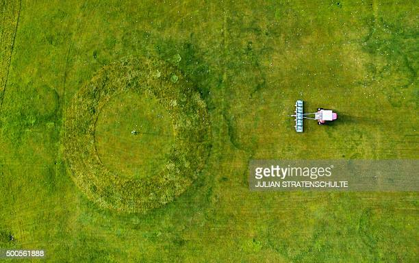 Aerial picture taken on December 9 shows a greenkeeper who collects golf balls of the driving range on a golf course in Rethmar central Germany...