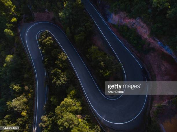 Aerial picture taken with drone flying over a stunning curved mountain road between the green woods and cliff formations in the Catalonia region.