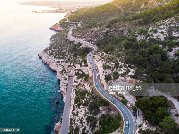 Aerial picture taken with drone flying over a traffic road in the coast with cliffs.