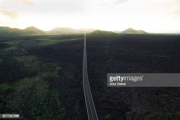 Aerial picture taken with drone flying over the beautiful Lanzarote island with volcano landscape and nice long straight road in the dark land with stunning sunset light.