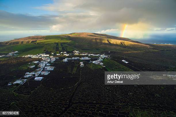 Aerial picture taken with drone flying over the Lanzarote volcanic island with nice landscape on countryside and beautiful rainbow on the ocean.