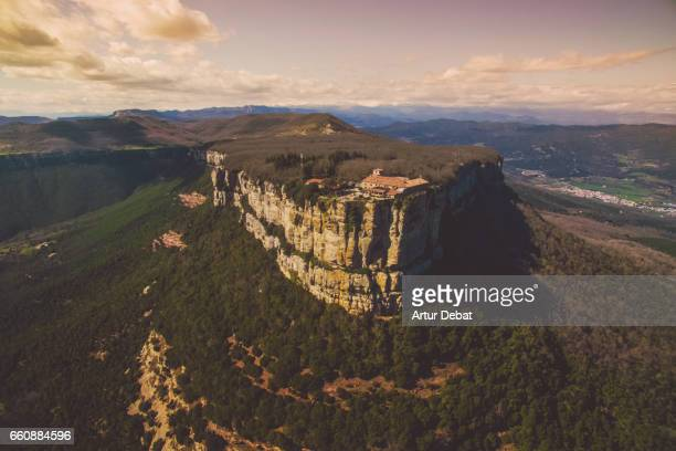 Aerial picture taken with drone flying over the stunning cliff landscape in the Catalonia region with sanctuary and church in the top of the cliff.