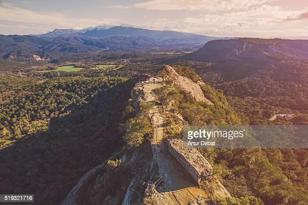 Aerial picture taken with drone of the people contemplating the views from the crag viewpoint in a stunning landscape in the Catalonia region.
