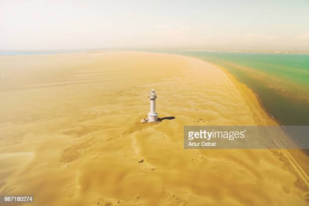 aerial picture taking with drone flying over a stunning white lighthouse in the middle of the desert sand dunes in the ebro delta shoreline with beach and the mediterranean sea. - delta del ebro fotografías e imágenes de stock