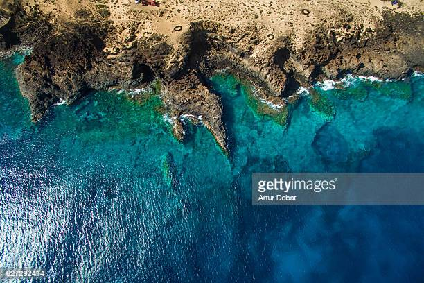 Aerial picture taking with drone flying over the Lanzarote volcanic island with beautiful shoreline created with lava and the blue water of the ocean.