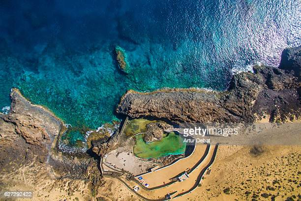 Aerial picture taking with drone flying over the Lanzarote volcanic island with beautiful shoreline created with lava and the blue water of the ocean with green pool.