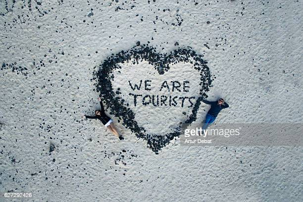 Aerial picture taking with drone of a couple traveling in the Lanzarote volcanic island laying on the sand beach with nice heart shape and letters made with volcanic rocks. We are tourists.