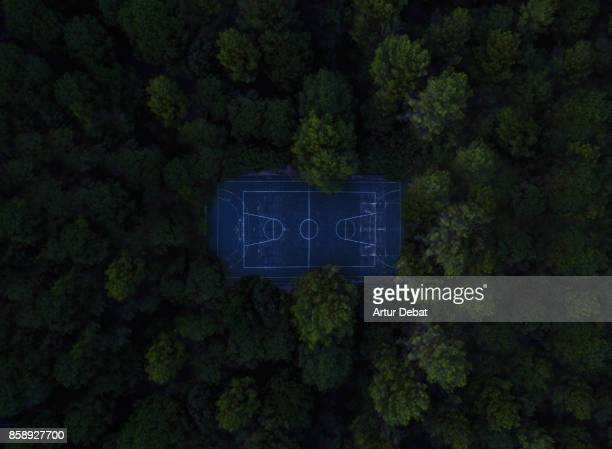 Aerial picture taking with drone of a stunning empty basketball court in the middle of the nature surrounded by the forest in visual and aesthetic picture taken from directly above view.