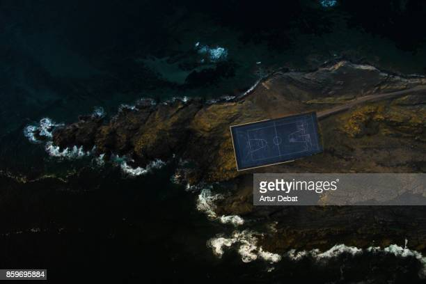 Aerial picture taking with drone of a stunning empty basketball court in the middle of an island surrounded by water and rocky terrain in visual and aesthetic picture taken from directly above view.