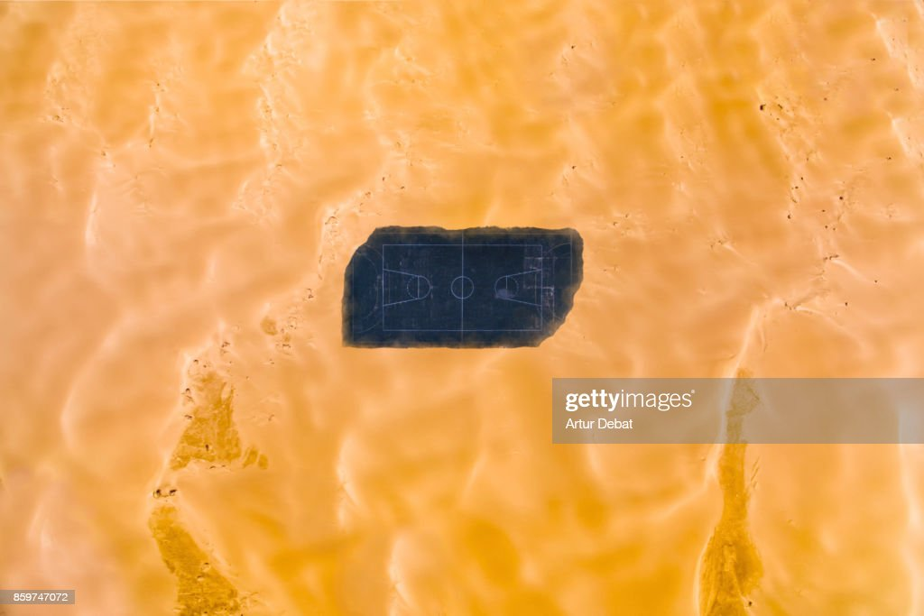 Aerial picture taking with drone of a stunning empty basketball court in the middle of the desert surrounded by dunes in visual and aesthetic picture taken from directly above view. : Stock Photo