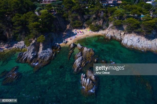 Aerial picture taking with drone of the beautiful Costa Brava on summer with nice little beach between rocks and people during travel vacations.