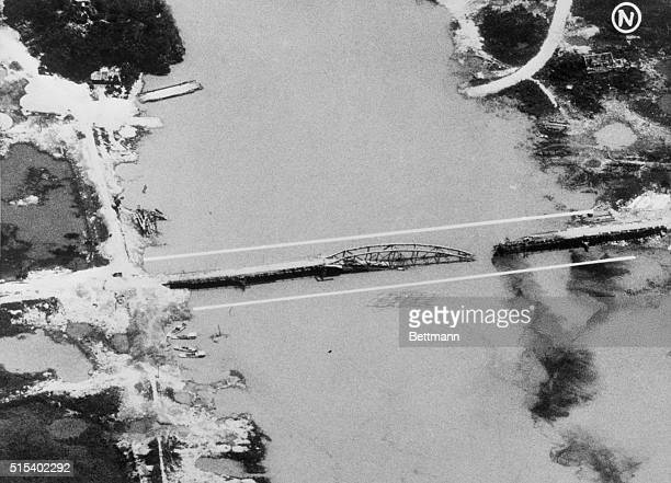 Aerial post strike photo of the railroad and highway bridge at Ninh Binh south of Hanoi in North Vietnam blown from its supporting pier and dropped...