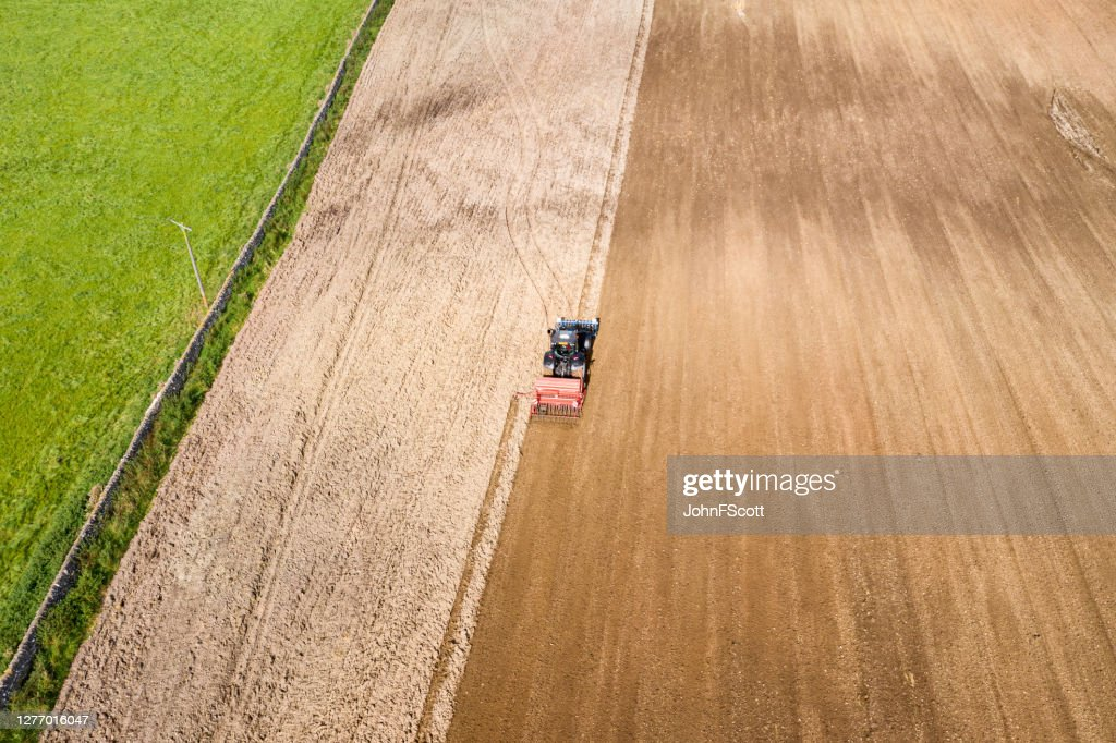 Aerial rear view of a tractor being used to pull a seed drill on a Scottish farm on a late summer day : Stock Photo