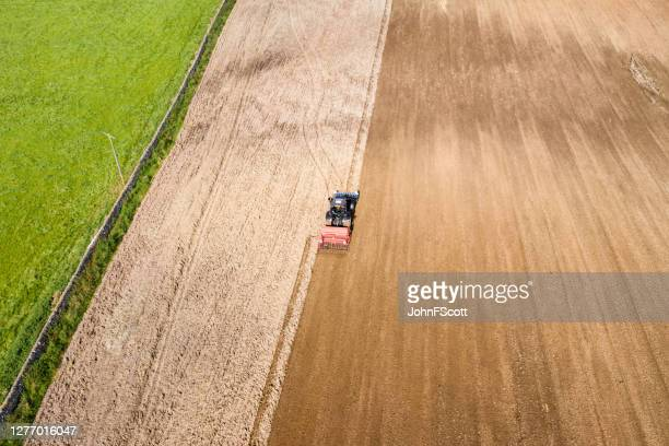 aerial rear view of a tractor being used to pull a seed drill on a scottish farm on a late summer day - johnfscott stock pictures, royalty-free photos & images