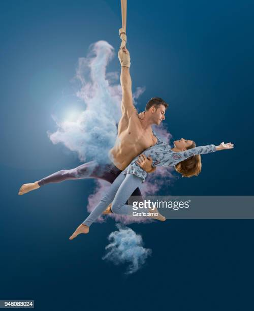 aerial rope artist couple performing in the air at circus - acrobatic activity stock photos and pictures