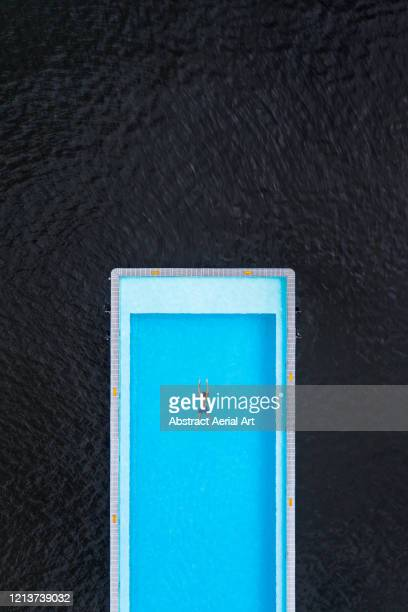 aerial shot above a person swimming in the badeschiff swimming pool, river spree, berlin, germany - symmetry stock pictures, royalty-free photos & images
