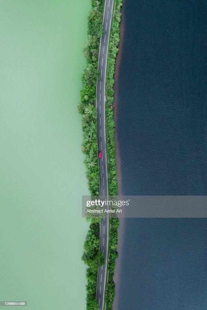 Aerial shot looking down on a red car crossing a road separating two lakes, Scottish Highlands, United Kingdom : Stock Photo