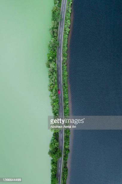 aerial shot looking down on a red car crossing a road separating two lakes, scottish highlands, united kingdom - vertical stock pictures, royalty-free photos & images