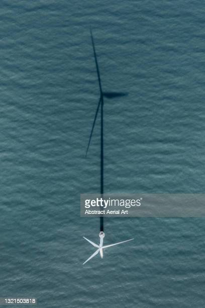 aerial shot looking down on an offshore wind turbine and its shadow, england, united kingdom - sea stock pictures, royalty-free photos & images