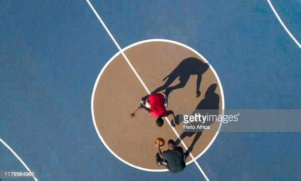 Aerial shot of 2 basketball players and shadows