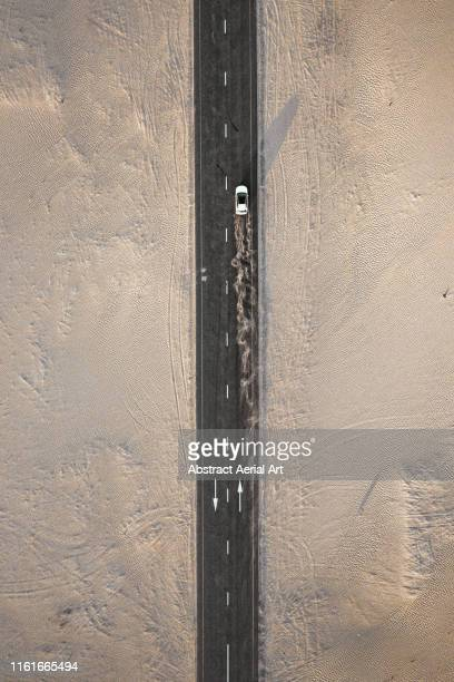 aerial shot of a dust trail from a moving vehicle on a desert road, united arab emirates - empty road stock pictures, royalty-free photos & images