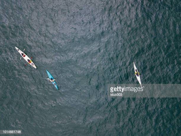 aerial shot of a small group of people sea kayaking - sea kayaking stock pictures, royalty-free photos & images