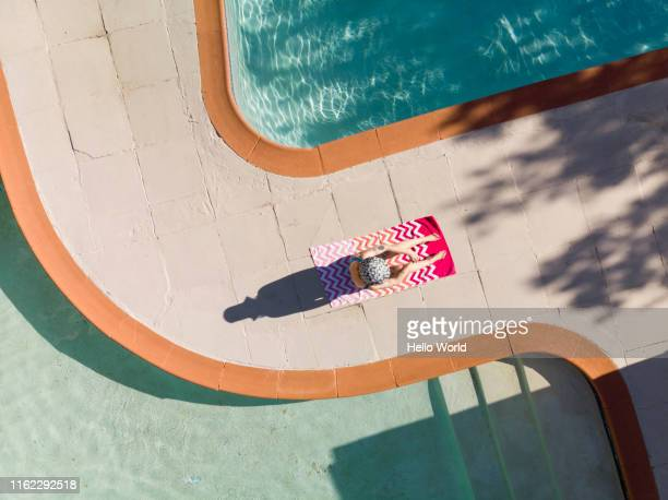 Aerial shot of a young woman seated sunbathing at poolside between two swimming pools