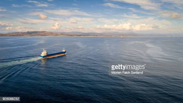 aerial shot of an oil tanker ship sailing in the waters of austrheim, norway summertime - tanker stock photos and pictures
