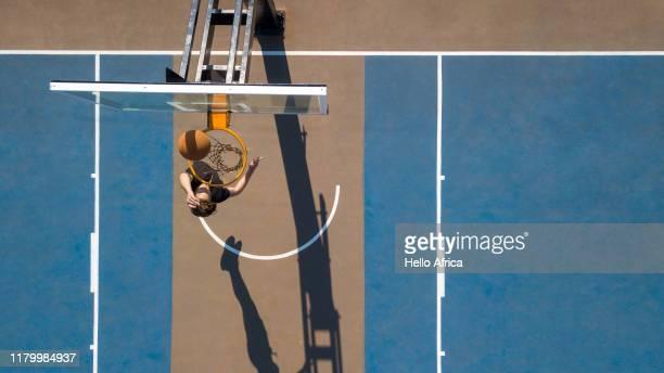 aerial shot of basketball making a hoop - korb werfen stock-fotos und bilder