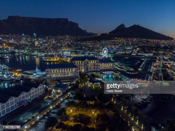 aerial shot of city with mountain in the background and ferris wheel lit at night - スポーツ施設 ストックフォトと画像