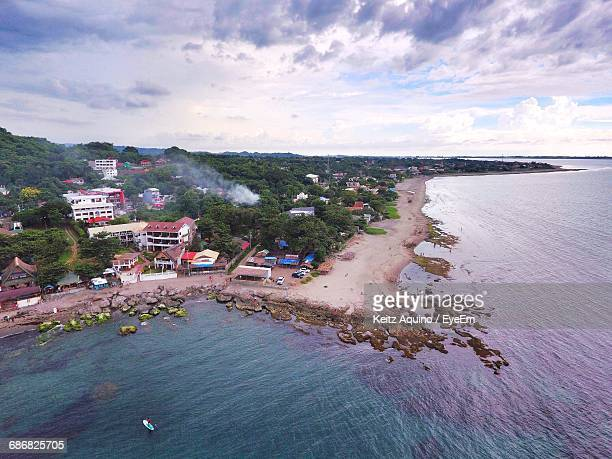 Aerial Shot Of Coastal Town Against Cloudy Sky