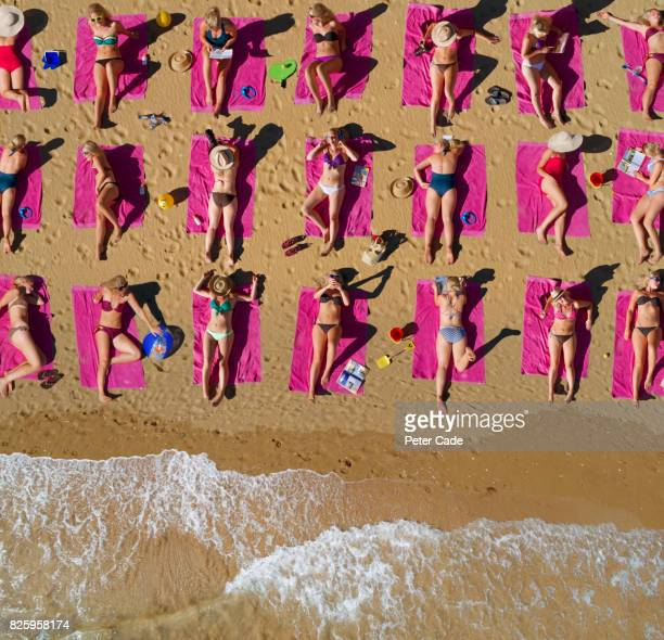 aerial shot of duplicated woman sunbathing on beach - sunbathing stock pictures, royalty-free photos & images