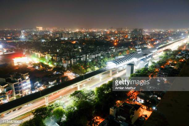 aerial shot of lights of delhi metro station with cityscape and traffic light trails in background - bangalore city stock pictures, royalty-free photos & images