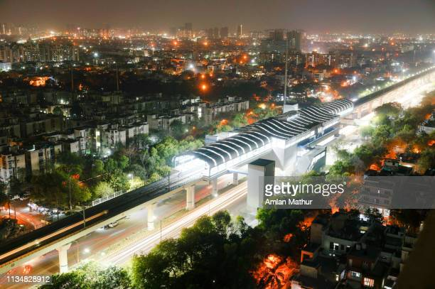 aerial shot of lights of delhi metro station with cityscape and traffic light trails in background - delhi stock pictures, royalty-free photos & images