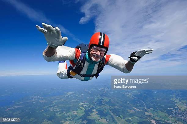 aerial shot of man skydiving - fallschirm stock-fotos und bilder