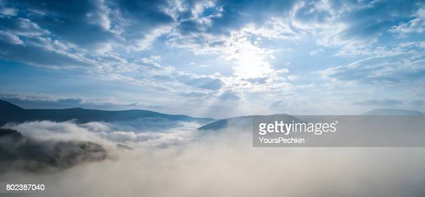 Aerial shot of mountain village under clouds