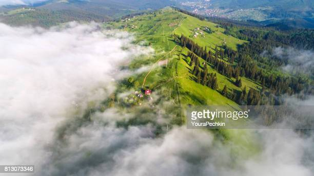 Aerial shot of mountain village under clouds
