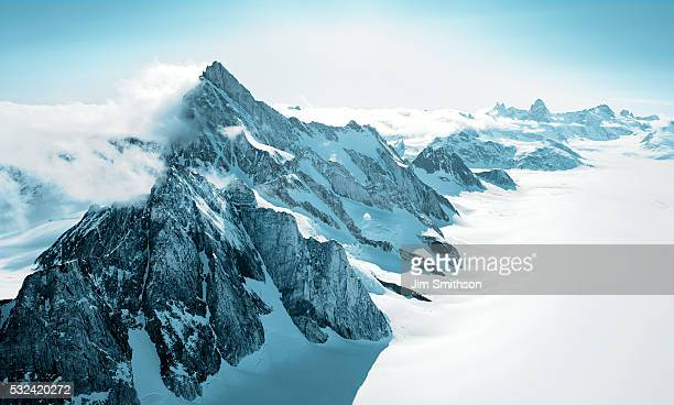 aerial shot of mountains covered with snow - glacier stock pictures, royalty-free photos & images