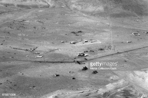 Aerial shot of roadways and structures in the desert taken from an airplane flying overhead Sinai Israel November 1967