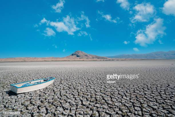 aerial shot of single boat ship on dried, cracked, dry, drought lakebed surface - greenpeace stock pictures, royalty-free photos & images